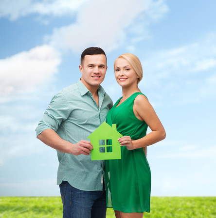 real estate, family and couple concept - smiling couple holding green paper house photo