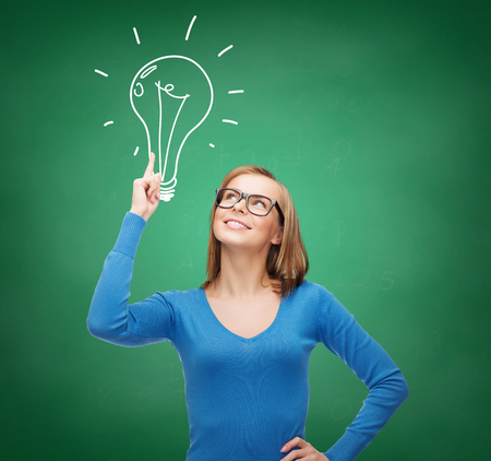 advertisement and electricity concept - attractive young woman in casual clothes and eyeglasses pointing her finger up to light bulb doodle photo
