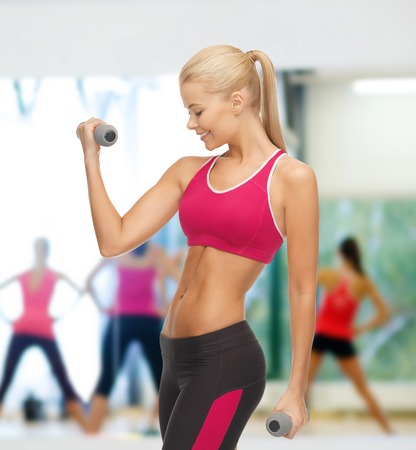 fitness and gym concept - young sporty woman with light dumbbells photo