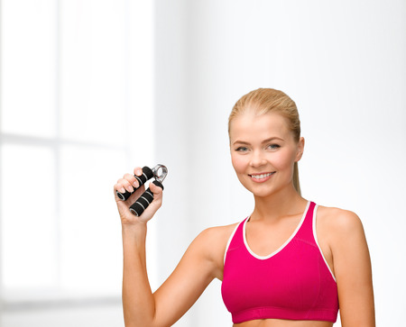 squeeze shape: fitness, healthcare and dieting concept - beautiful sporty woman with hand expander