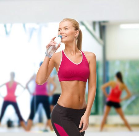 pumping: fitness, healthcare and dieting concept - smiling sporty woman with bottle of water Stock Photo