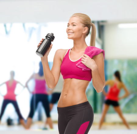 six packs: fitness, healthcare and dieting concept - smiling sporty woman drinking water from sportsman bottle