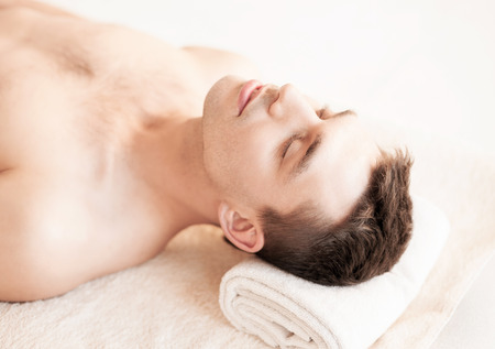 health resort treatment: close up of man face in spa salon