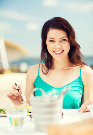 food, summer holidays and vacation - girl eating in cafe on the beach photo