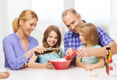 a little dinner: food, family, children, hapiness and people concept - happy family with two kids making dinner at home Stock Photo