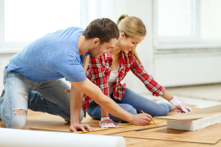 wood floor: repair, building and home concept - smiling couple measuring wood flooring