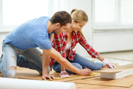 reparatie, bouw en huis concept - lachende paar meten houten vloeren