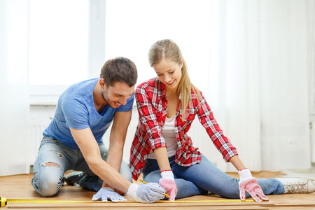 woman measuring: repair, building and home concept - smiling couple measuring wood flooring