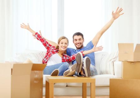 bewegen, thuis en paar concept - lachende paar ontspannen op de bank in het nieuwe huis
