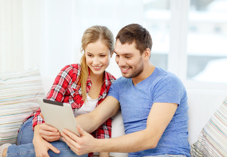 home, technology and relationships concept - smiling couple with tablet pc computer at home photo