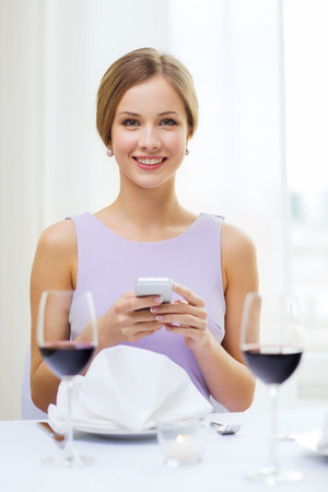 reastaurant, technology and happiness concept - smiling young woman with smartphone and glass of red wine at restaurant photo