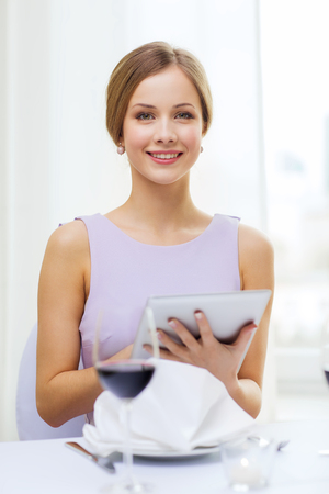 reviewer: reastaurant, technology and happiness concept - smiling young woman with tablet pc computer and glass of red wine at restaurant
