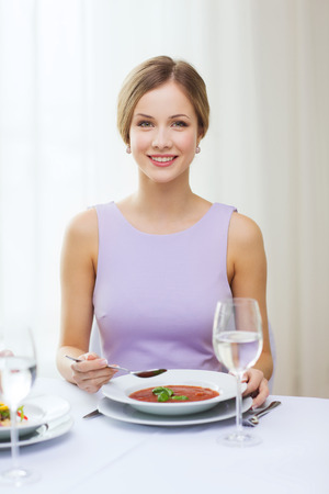 person appetizer: restaurant, people and holiday concept - smiling young woman eating appetizer at restaurant Stock Photo