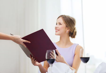 recieving: reastaurant and happiness concept - smiling young woman recieving menu from waiter at restaurant