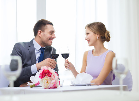 up to date: restaurant, couple and holiday concept - smiling young couple with glasses of red wine looking at each other at restaurant
