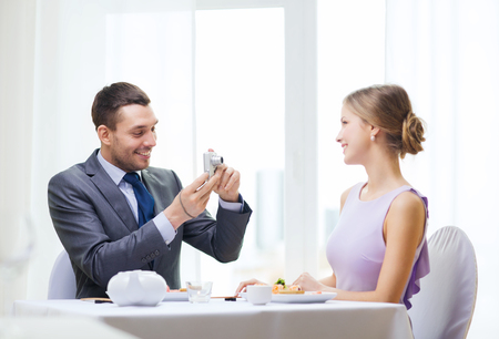 restaurant, couple, technology and holiday concept - smiling man taking picture of wife or girlfriend with digital camera at restaurant photo