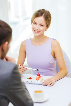 restaurant, couple and holiday concept - smiling woman eating dessert and looking at husband or boyfriend at restaurant photo