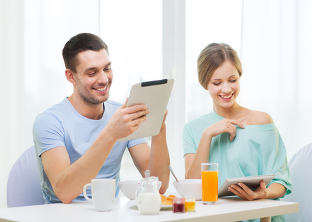 having breakfast: food, home, couple and technology concept - smiling couple with tablet pc reading news and having breakfast at home