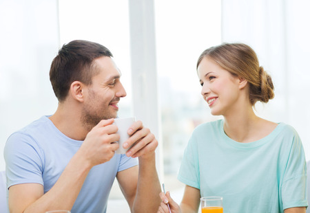 having breakfast: food, home, couple and happiness concept - smiling couple having breakfast at home Stock Photo