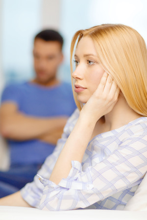love, family and happiness concept - upset young woman with man on the back at home photo