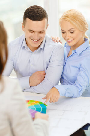 home, designe and architecture concept - smiling couple looking at blueprint and color samples at office photo