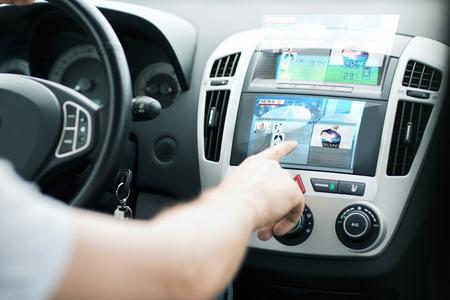 réseautage: transport et le concept de véhicule - l'homme à partir du panneau de contrôle de la voiture pour lire les nouvelles