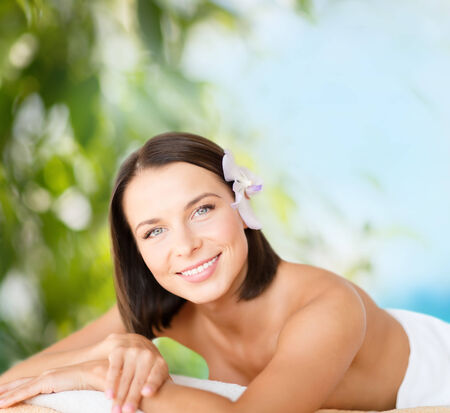 health and beauty, resort and relaxation concept - beautiful woman with flower in her hair in spa salon lying on the massage desk photo