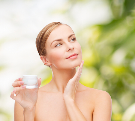 cosmetics, health and beauty concept - beautiful woman applying cream on her skin