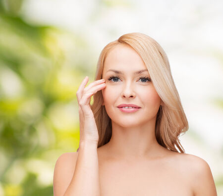 heath and beauty concept - face of beautiful woman touching her eye area photo