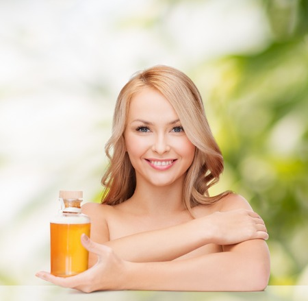 shampoo bottle: health and beauty concept - happy woman with oil bottle Stock Photo