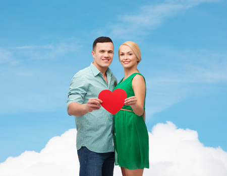 couple, love and family concept - smiling couple holding big red heart photo