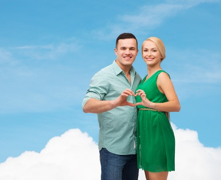love and family concept - smiling couple showing heart with hands photo