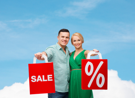 happiness, shopping and couple concept - smiling couple with shopping bags with sale and percent sign photo