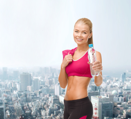 fitness, healthcare and dieting concept - smiling sporty woman with bottle of water and towel photo