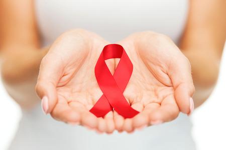 의료 및 의학 개념 - 여성 손 들고 빨간색 에이즈 인식 리본