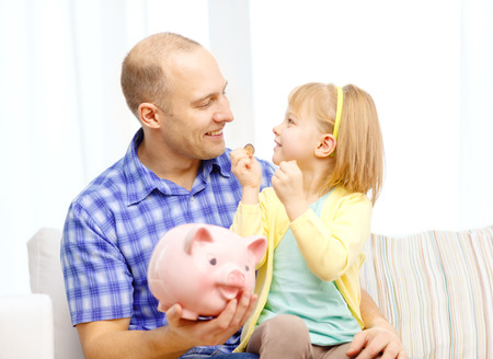 investmen: family, children, money, investmen and happy people concept - happy father and daughter with big pink piggy bank Stock Photo