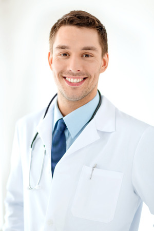healthcare and medical concept - young male doctor with stethoscope in hospital photo