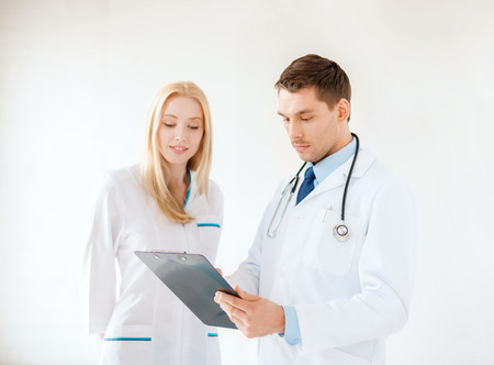 healthcare and medical concept - smiling young male doctor with stethoscope and clipboard and female nurse in hospital photo