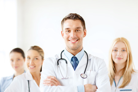 male doctor: healthcare and medicine concept - attractive male doctor in front of medical group in hospital