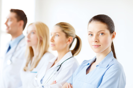 healthcare and medicine concept - female doctor or nurse in front of medical group in hospital