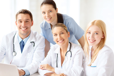 healthcare, medical and technology concept - smiling group of doctors with laptop computer in hospital Stock Photo