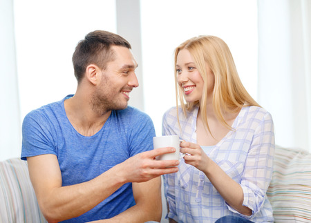 love, family, healthy food and happiness concept - smiling man giving cup of tea or coffee to wife or girlfriend at home photo