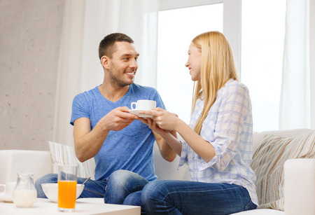 love, family, healthy food and happiness concept - smiling man giving his girlfriend or wife cup of coffee at home photo