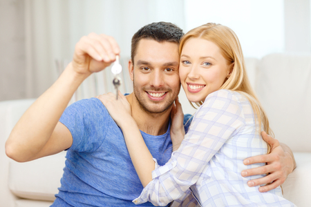 real estate, family and couple concept - smiling couple holding keys at home photo
