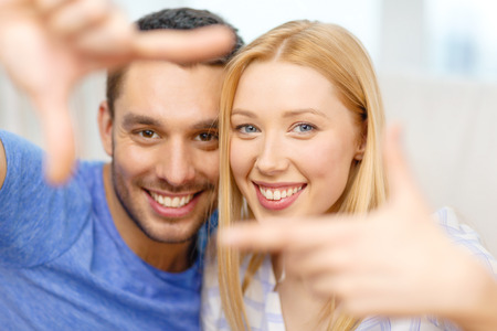 love, family and happiness concept - smiling happy couple making frame gesture at home photo