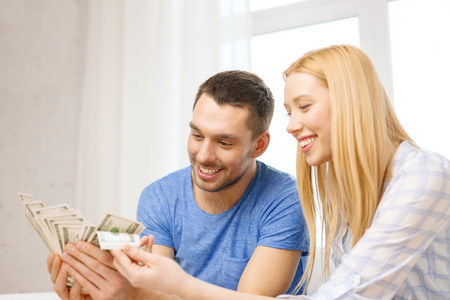 love, family, finance, money and happiness concpet - smiling couple with money at home