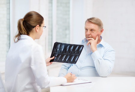 healthcare, medicine and elderly concept - female doctor with old man looking at x-ray photo