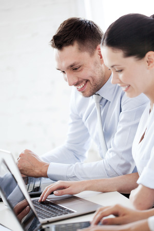 business concept - smiling businesswoman and businessman working with laptop in office photo