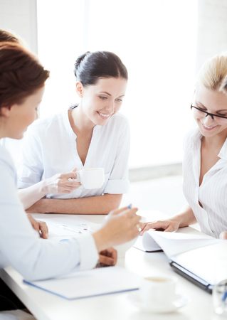 business concept - smiling businesswoman with team on meeting in office photo