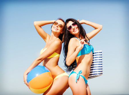 summer holidays, vacation and beach activities - girls with ball on the beach photo